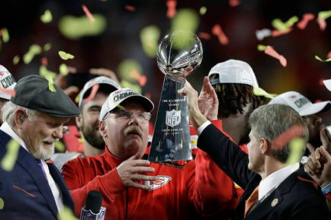 Kansas City Chiefs chairman Clark Hunt, right, hands the trophy to head coach Andy Reid after t ...