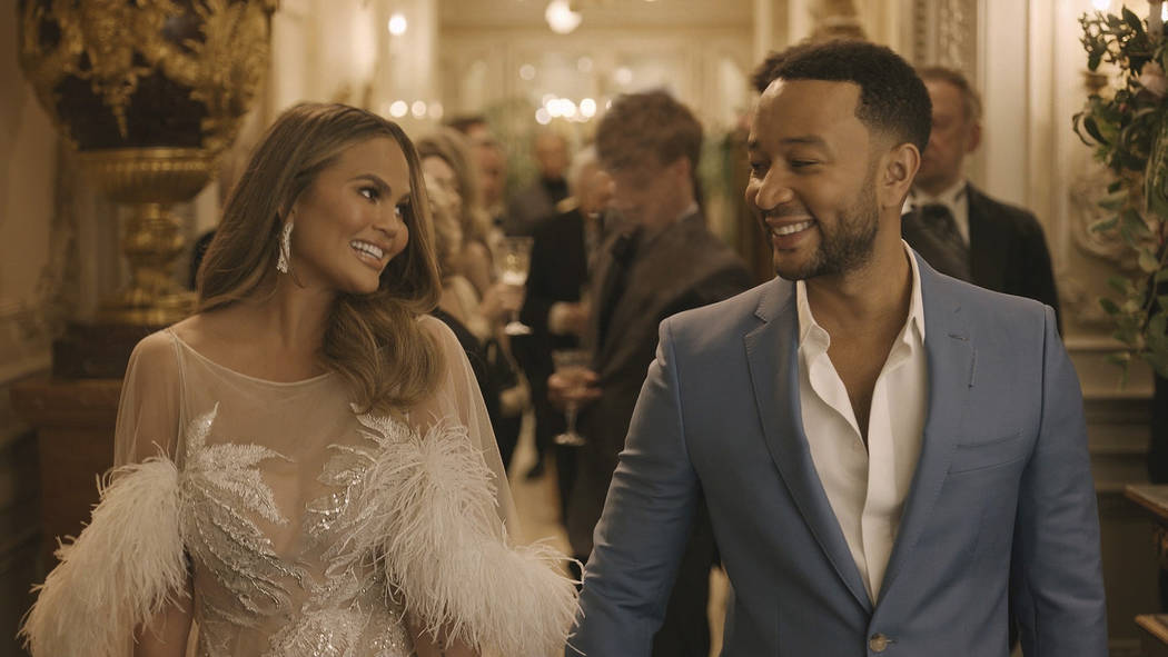 This undated image provided by Genesis shows Chrissy Teigen and her husband John Legend in a sc ...