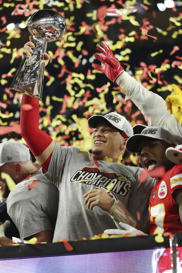 Kansas City Chiefs quarterback Patrick Mahomes (15) holds up the Vince Lombardi Trophy after th ...