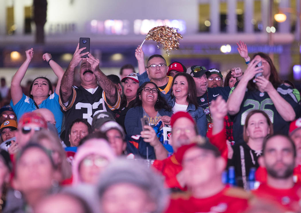 The crowd cheers for the half time show at a watch party for Super Bowl LIV at the Downtown Las ...