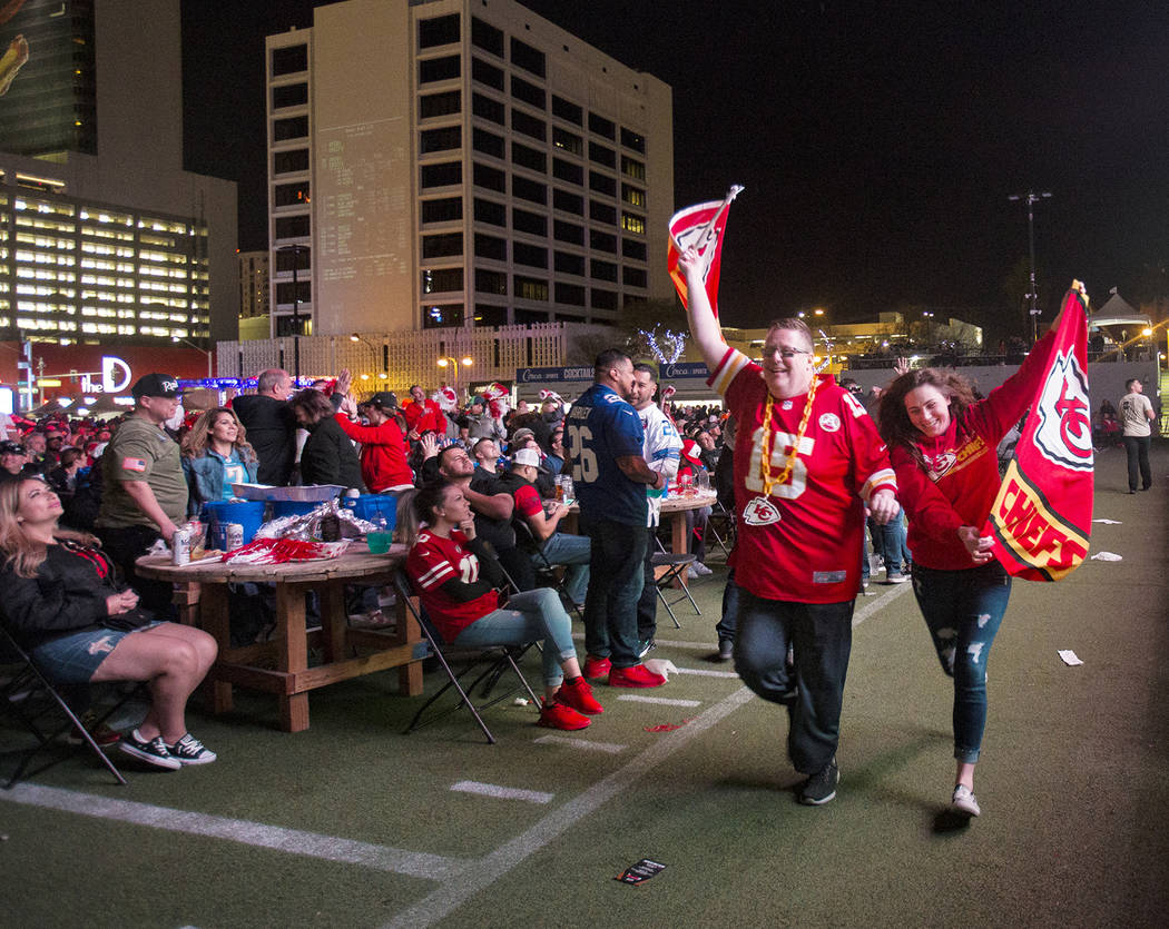 Steven Foster and Jane Fry, both of Kansas City, run a Kansas City Chiefs flag in front of the ...