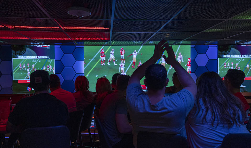 Individuals watch the NFL Super Bowl 54 football game between the San Francisco 49ers and Kansa ...