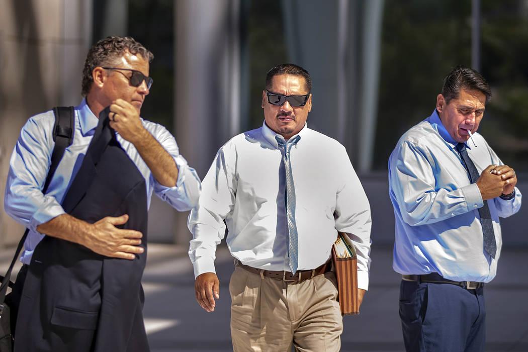 Lawyer Mark Fleming, left, walks with defendant Albert Lopez, past defendant Bradley Campos, ou ...