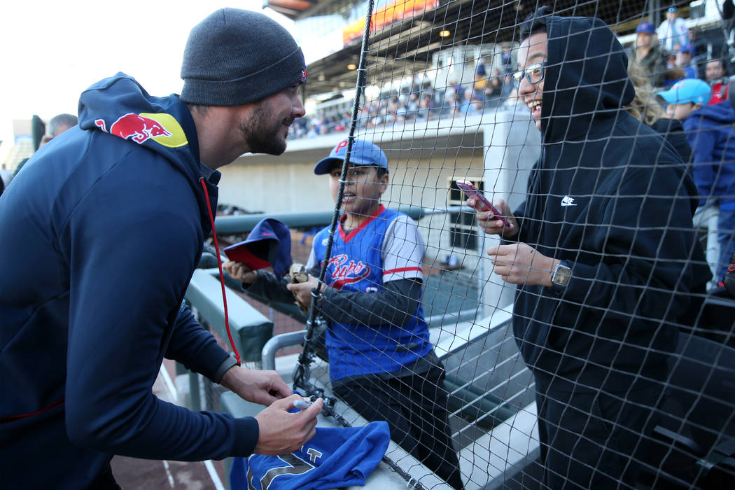 Chicago Cubs player Kris Bryant signs an autograph for Marco Valdovinos, right, 15, and Steve M ...