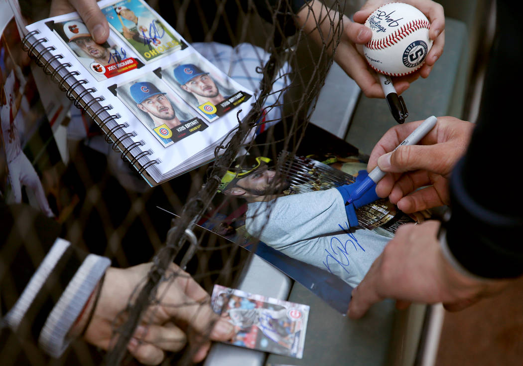 Chicago Cubs player Kris Bryant signs autographs for people during a live batting practice even ...