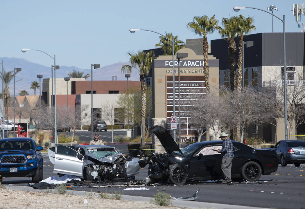 Investigators work at the scene of a fatal collision at the intersection of South Fort Apache ...
