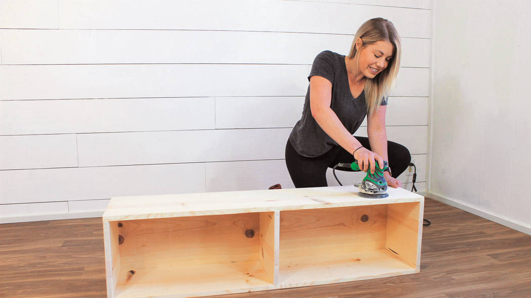 Liz Spillman uses a sander to eliminate any sharp edges, rough areas and any wood filler. (Kate ...