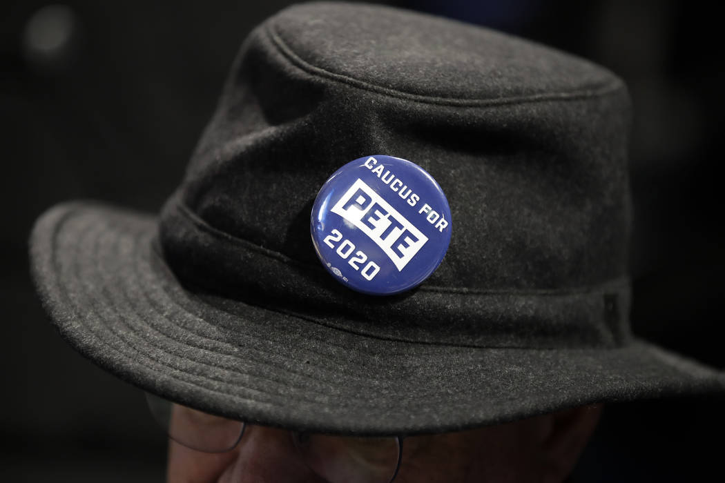 A caucus goer wears a button for Democratic presidential candidate former South Bend, Ind., May ...