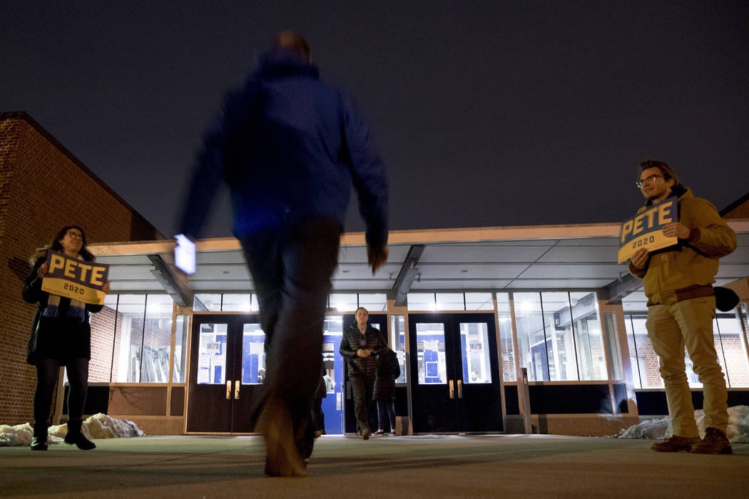 People arrive for caucus at Roosevelt Hight School, Monday, Feb. 3, 2020, in Des Moines, Iowa. ...