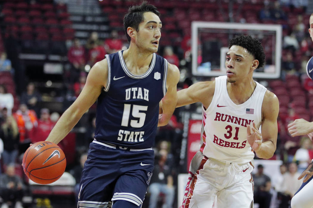 Utah State's Abel Porter (15) drives around UNLV's Marvin Coleman (31) during the first half of ...