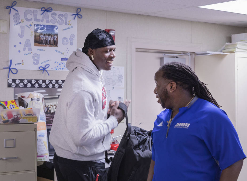 Desert Pines High School's wide receiver senior Darnell Washington, left, and assistant coach a ...