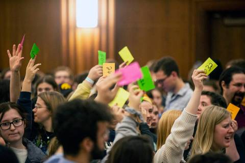 University of Iowa students hold up numbered cards while they caucus, Monday, Feb. 3, 2020, at ...