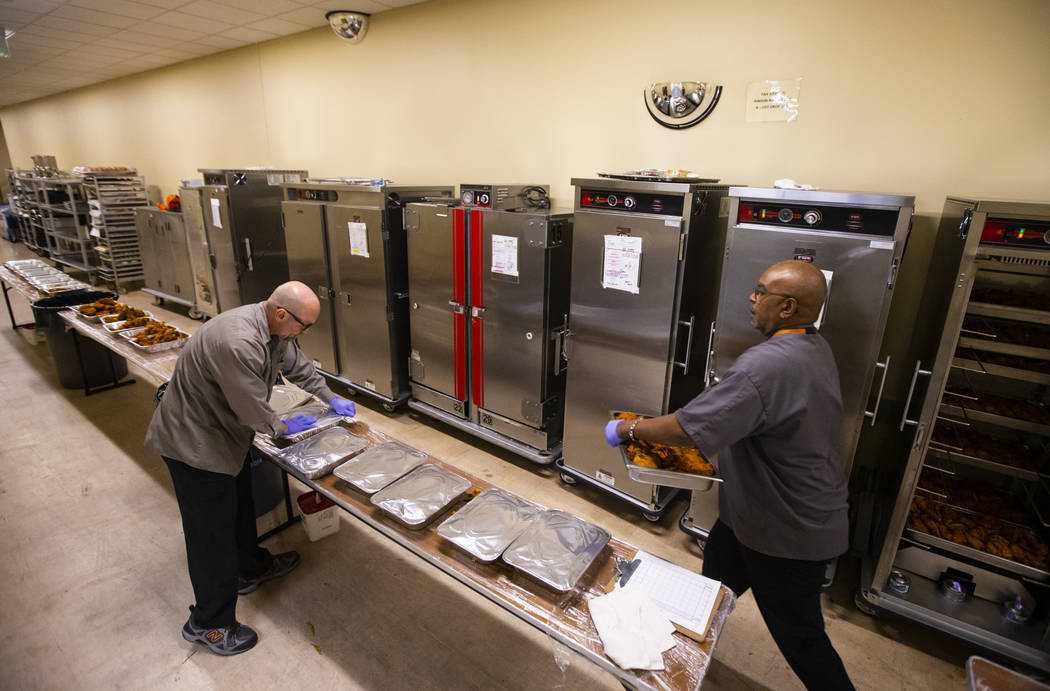 Bob Ayouba, left, and Sarif El-Amin, of Three Square food bank, package fried chicken and other ...