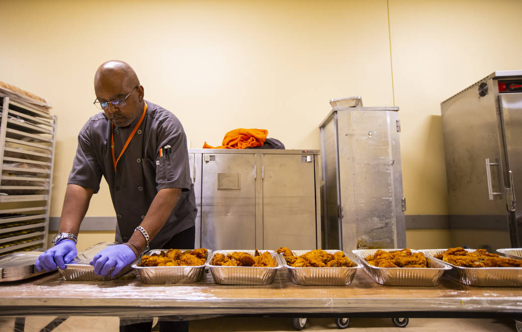 Sarif El-Amin, of Three Square food bank, packages fried chicken and other surplus banquet food ...