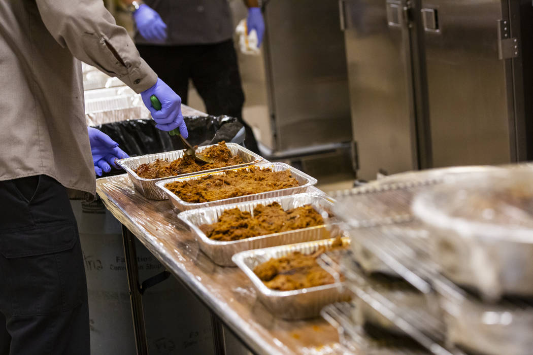 Bob Ayouba, of Three Square food bank, packages beef brisket and other surplus banquet food fro ...