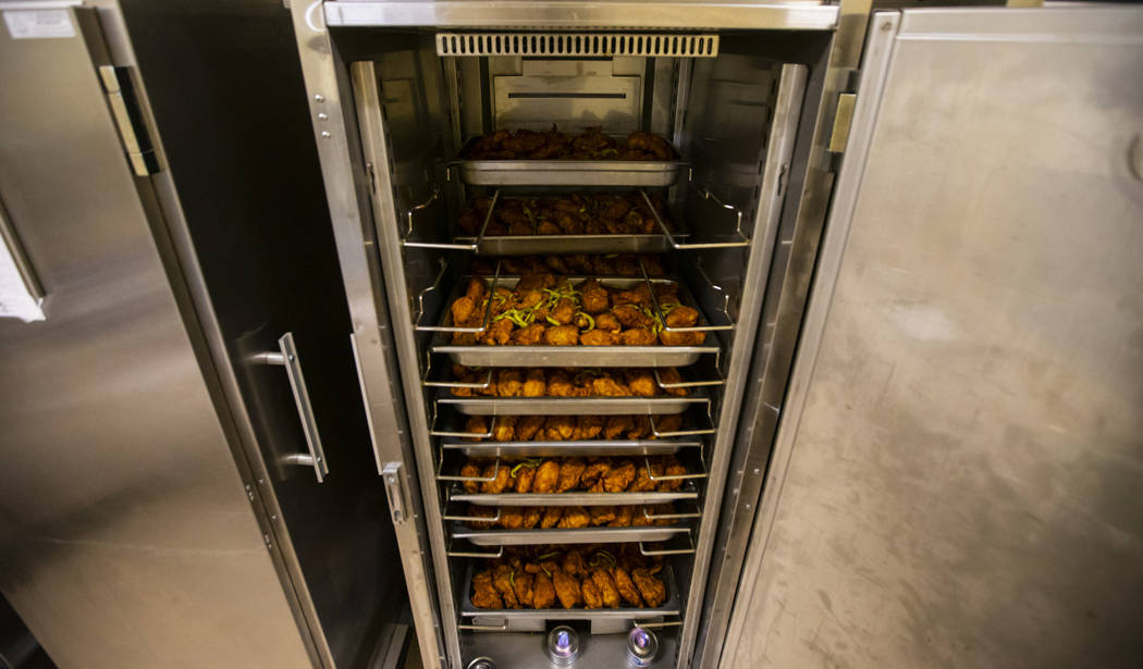 Racks of fried chicken to be donated to Three Square food bank, as part of the surplus banquet ...