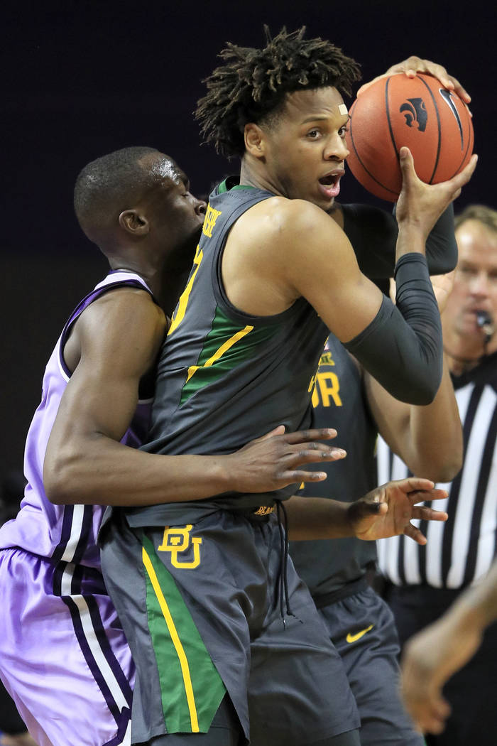 Baylor forward Freddie Gillespie, right, is covered by Kansas State forward Makol Mawien, left, ...