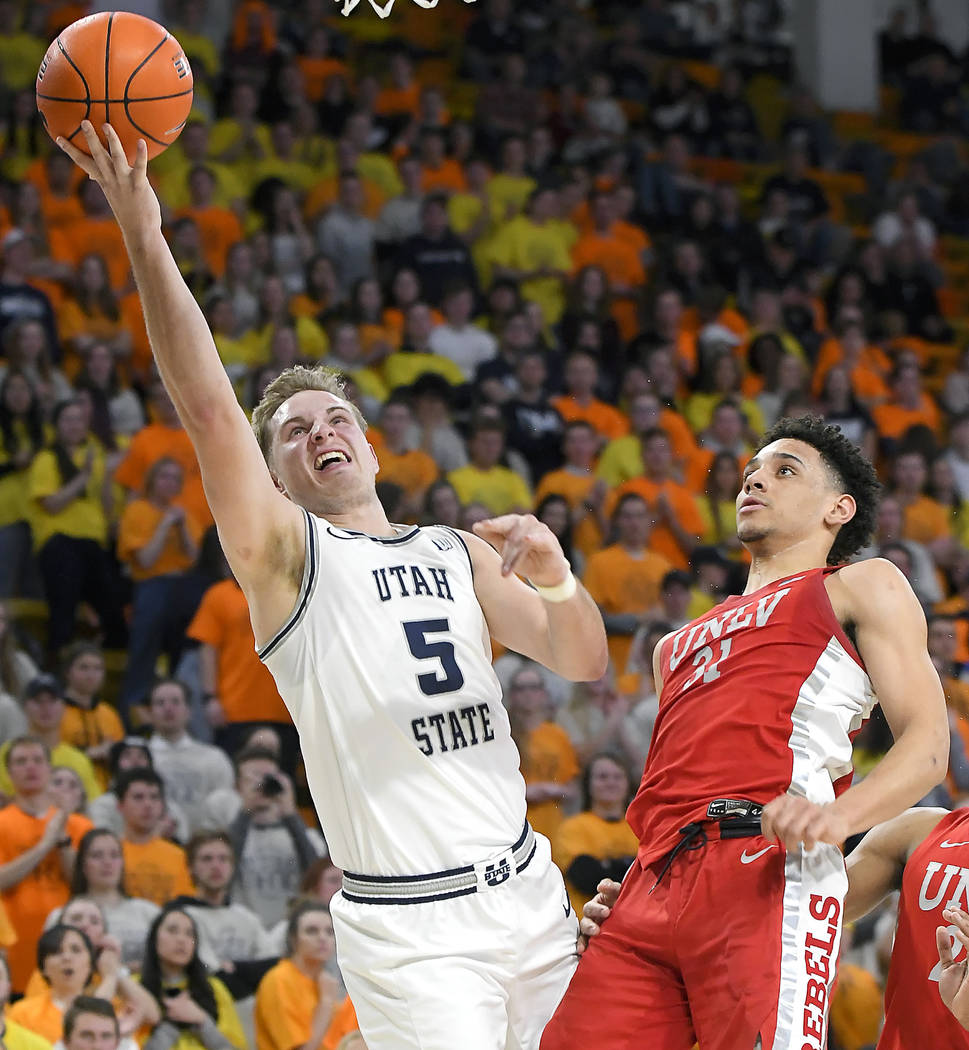 Utah State guard Sam Merrill (5) shoots next to UNLV guard Marvin Coleman (31) during the first ...