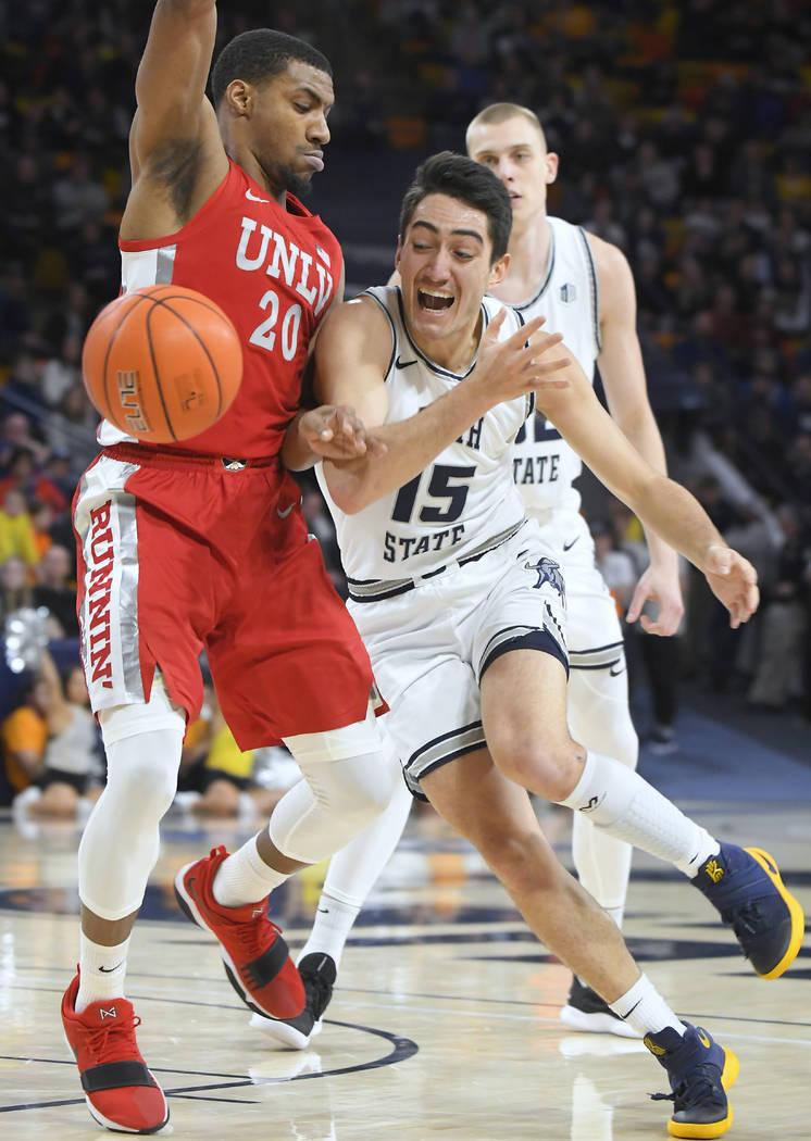 Utah State guard Abel Porter (15) loses control of the ball as UNLV forward Nick Blair (20) def ...