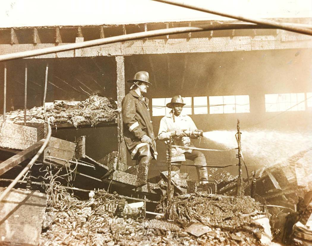 Fire Capt. Charlie Smith (right) extinguishes a fire. (Courtesy of Westside School Alumni Found ...