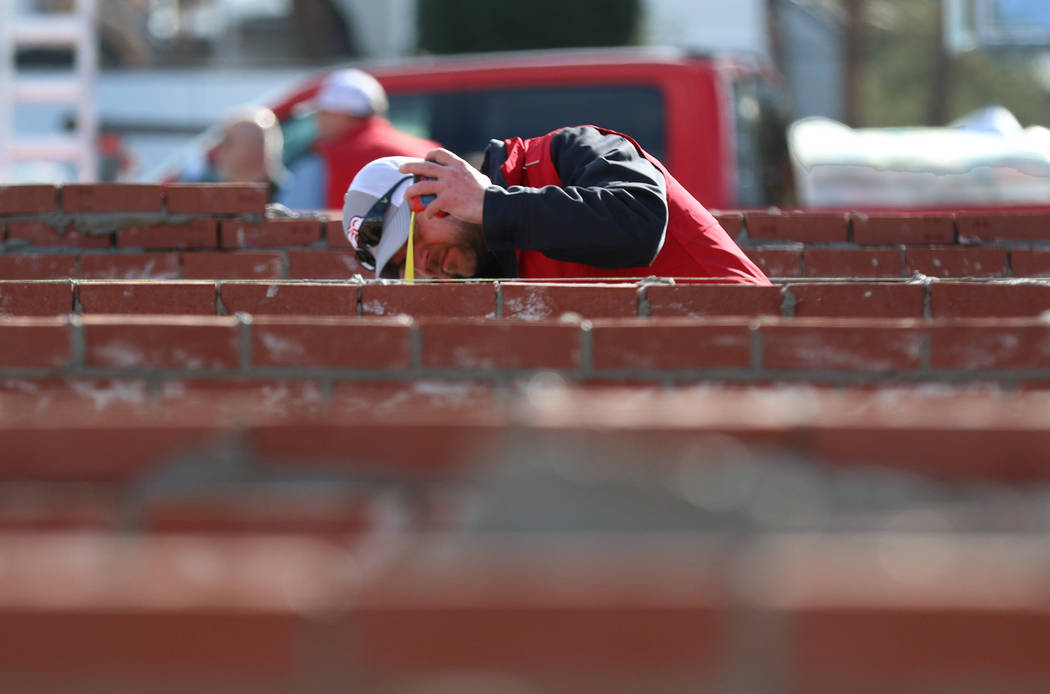Judge David Pryes of Greenway, Wis, inspects a brick wall during the 2020 Spec Mix Bricklayer 5 ...