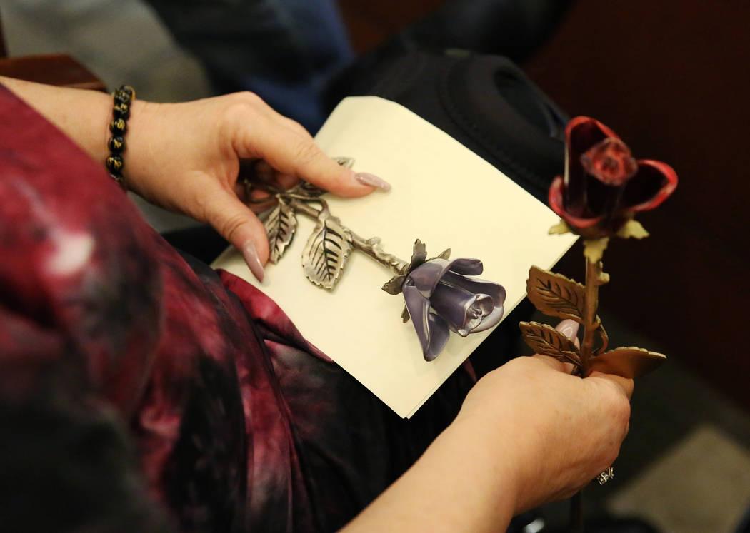 Theresa Christensen, mother of Lee's Liquor robbery victim Matthew Christensen, 24, holds her v ...