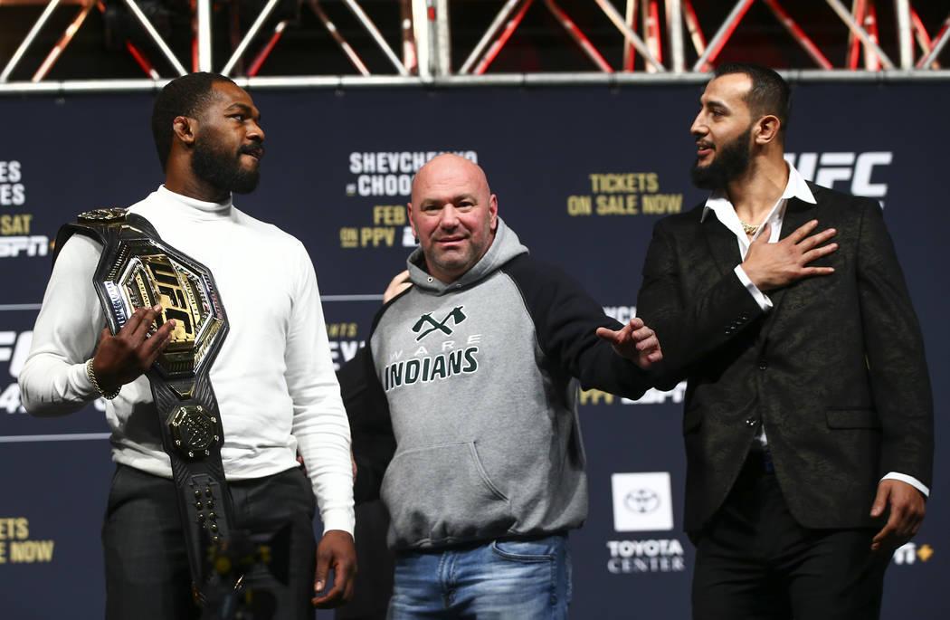 UFC President Dana White, center, looks on as Jon Jones, left, and Dominick Reyes face off duri ...