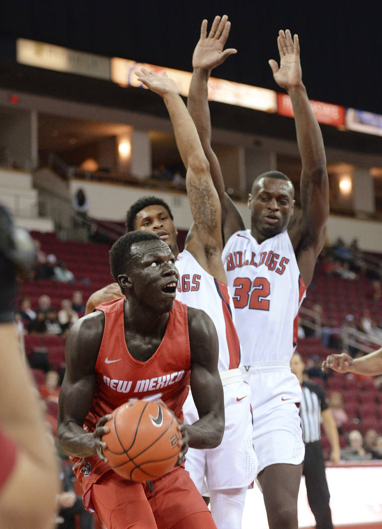 New Mexico's Makuach Maluach, left, looks to go to the hoop against Fresno State's Nate Grimes, ...
