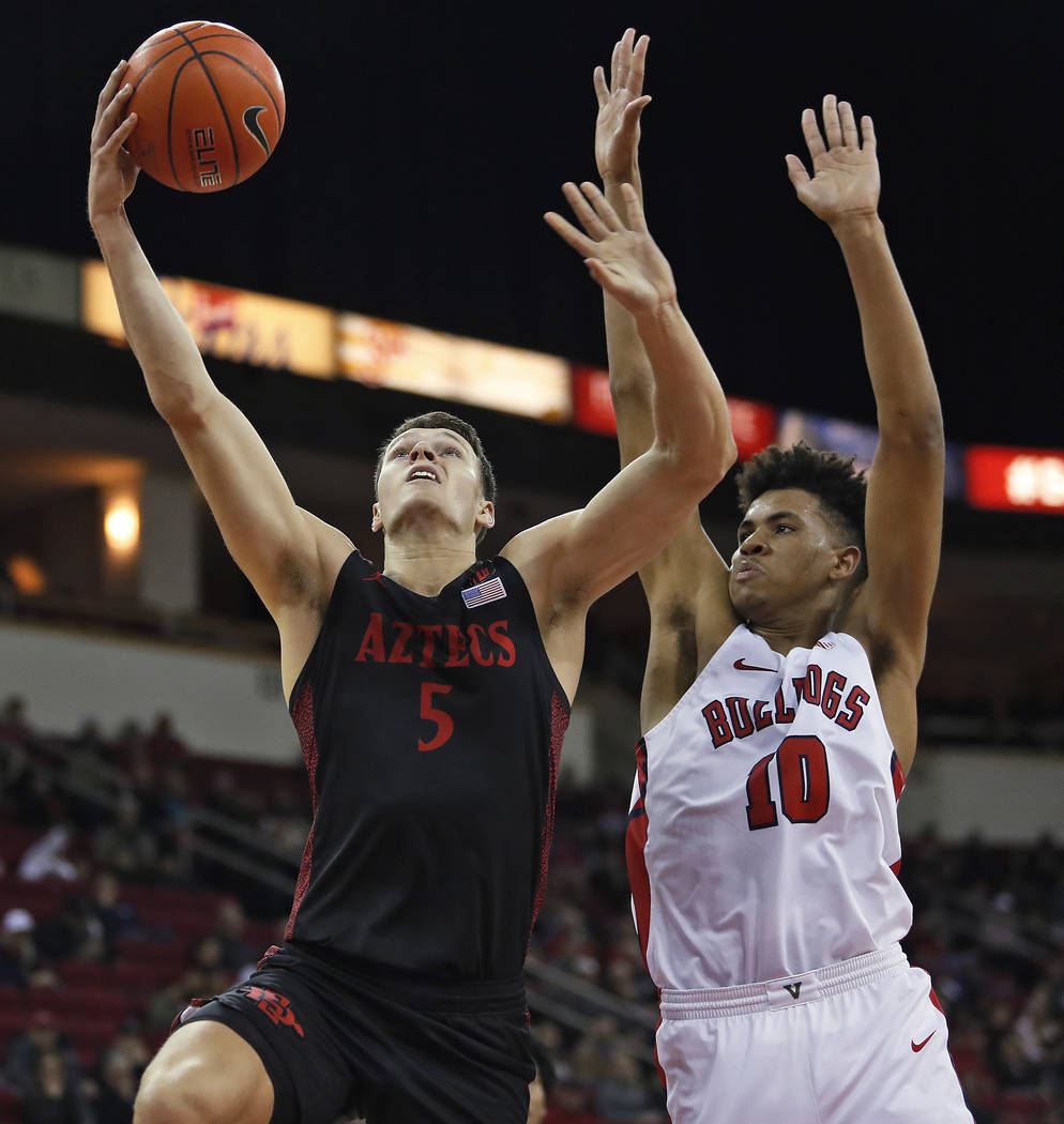 San Diego State's Yanni Wetzell shoots next to Fresno State's Orlando Robinson during the first ...