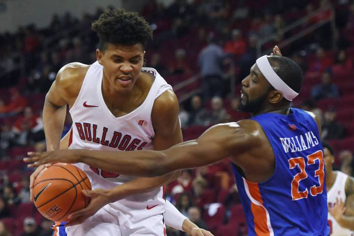 Boise State's RJ Williams, right, gets a hand on the ball carried by Fresno State's Orlando Rob ...