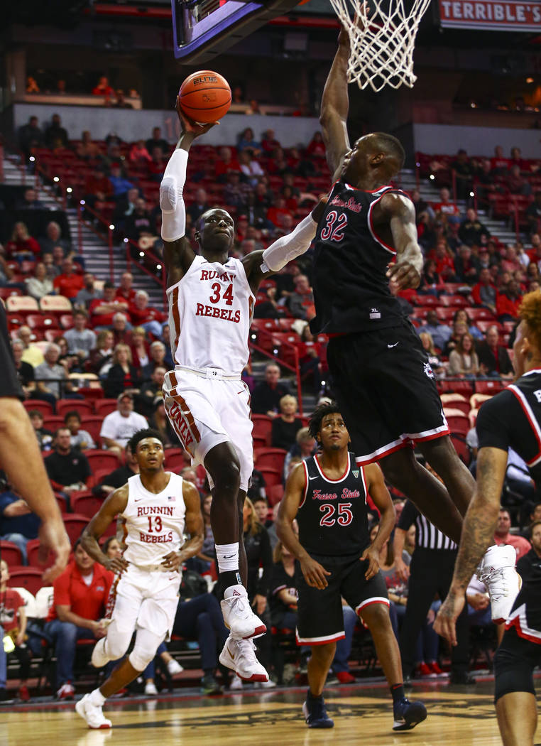UNLV's Cheikh Mbacke Diong (34) goes to the basket against Fresno State's Nate Grimes (32) duri ...