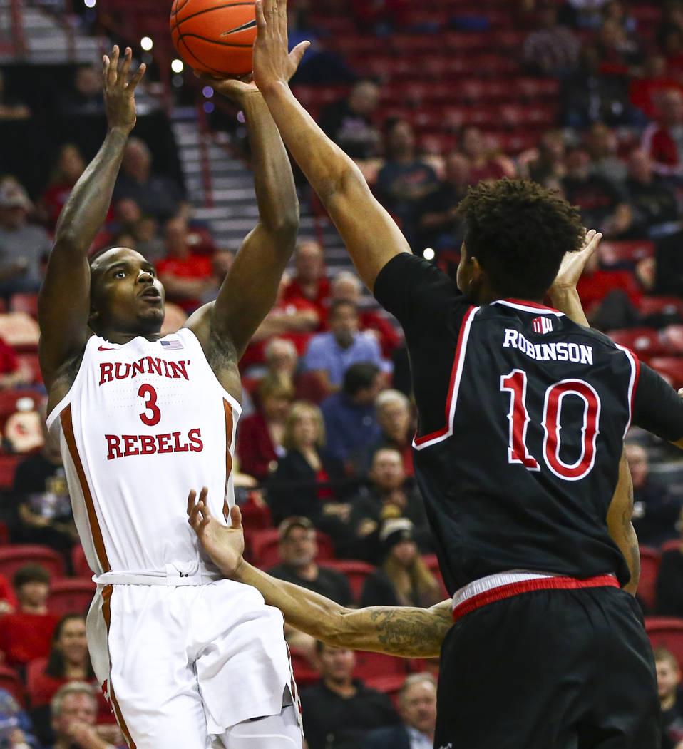 UNLV's Amauri Hardy (3) shoots over Fresno State's Orlando Robinson (10) during the first half ...