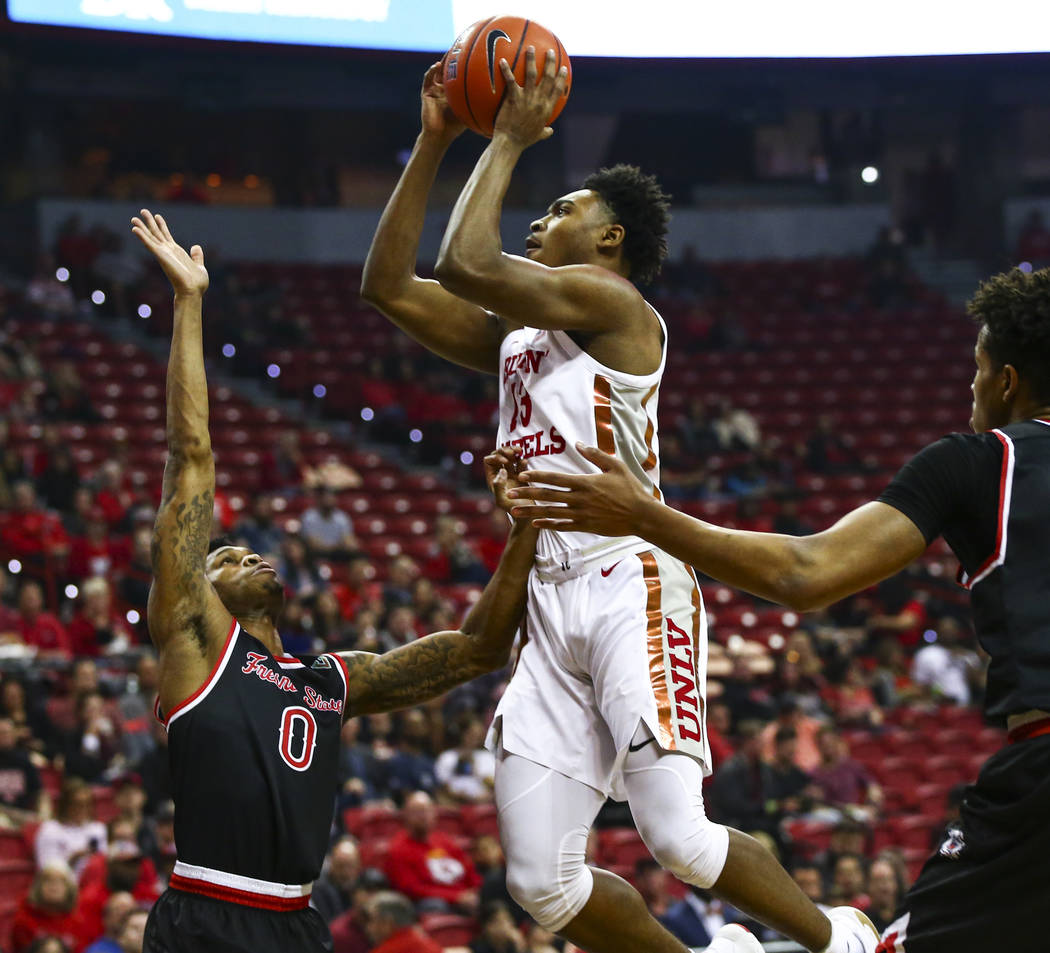 UNLV's Bryce Hamilton (13) shoots over Fresno State's New Williams (0) during the first half of ...