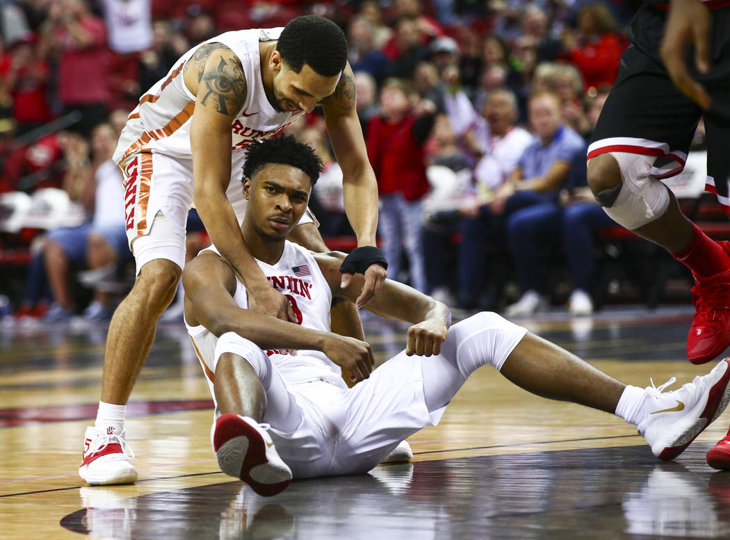 UNLV's guard Bryce Hamilton, center, reacts with teammate Elijah Mitrou-Long (55) after drawing ...