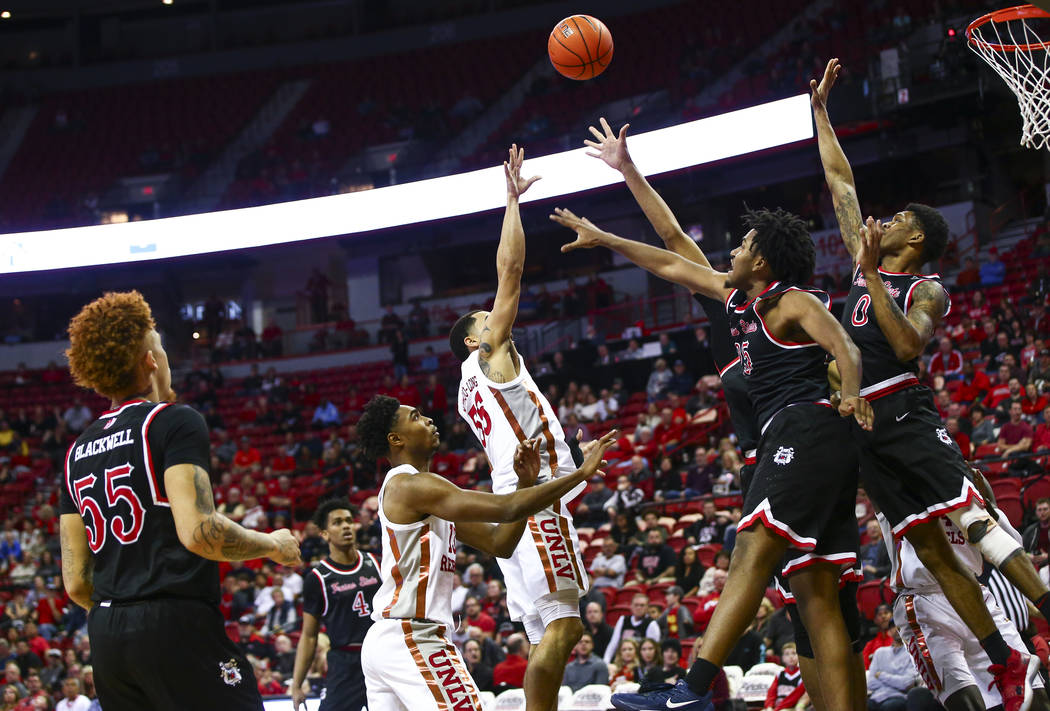 UNLV's Elijah Mitrou-Long (55) sends the ball over Fresno State's Anthony Holland (25) and New ...