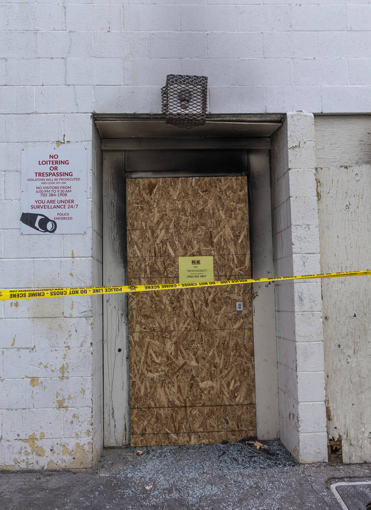 The broken rear glass door of the Alpine Motel Apartments is boarded up and lined with crime ta ...
