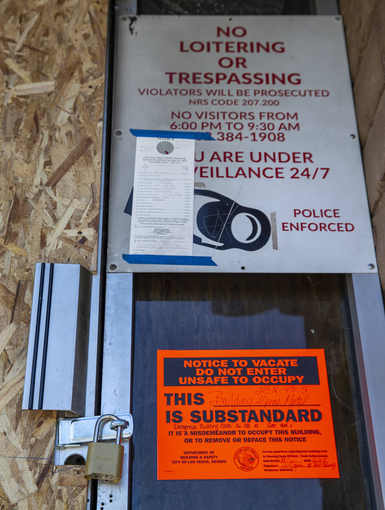 The front door is padlocked and marked with a dangerous building sign issued by the City of Las ...