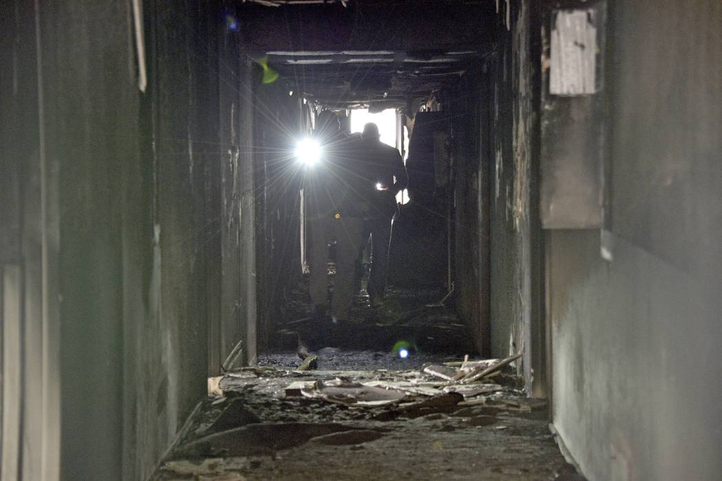 Investigators walk through an interior corridor after a fire at a three-story apartment complex ...