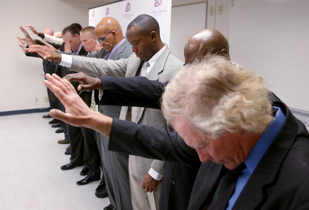 Michael Moore, third from right, prays with his fellow graduates during his Renewing Hope progr ...