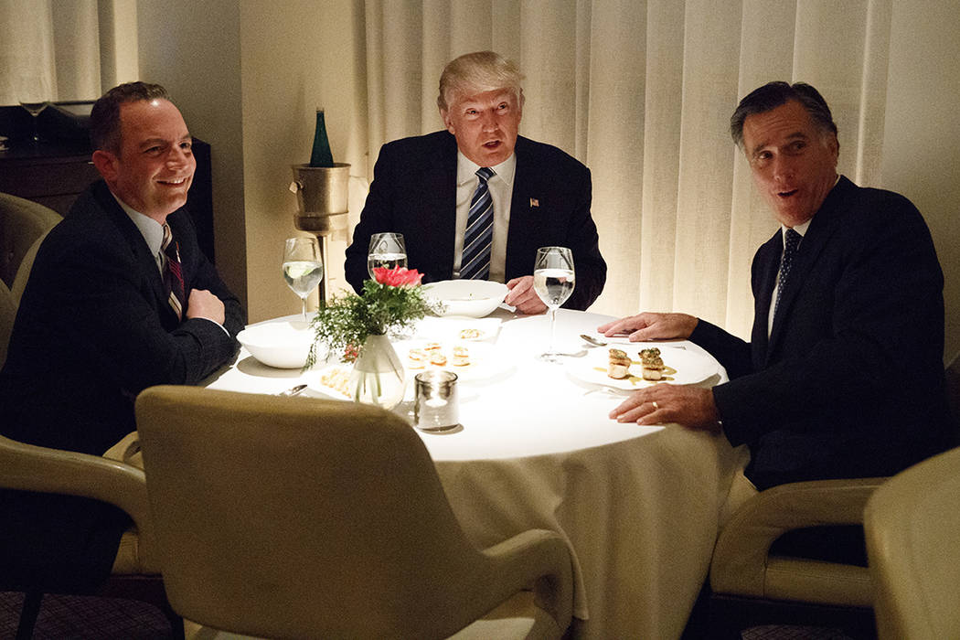 President-elect Donald Trump, center, eats dinner with Mitt Romney, right, and Trump Chief of S ...