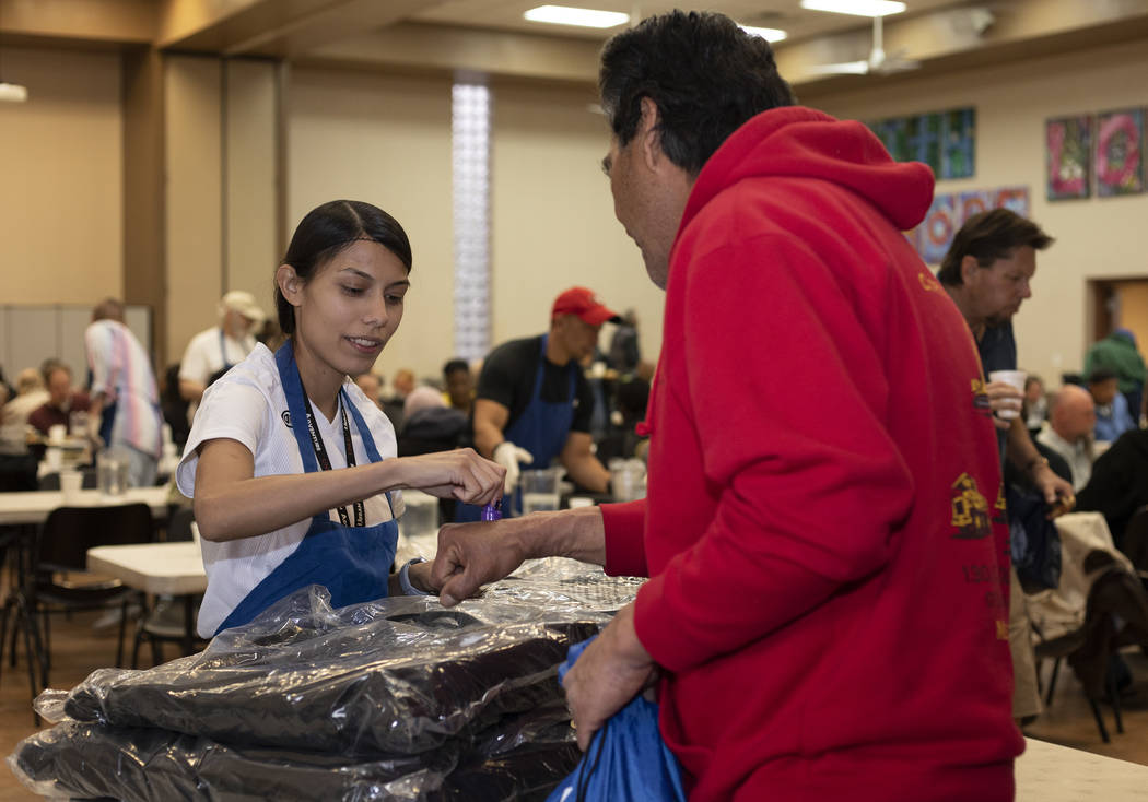 Volunteer Vicky Castellanos hands out CITYPAK backpacks at the Las Vegas Rescue Mission on Satu ...