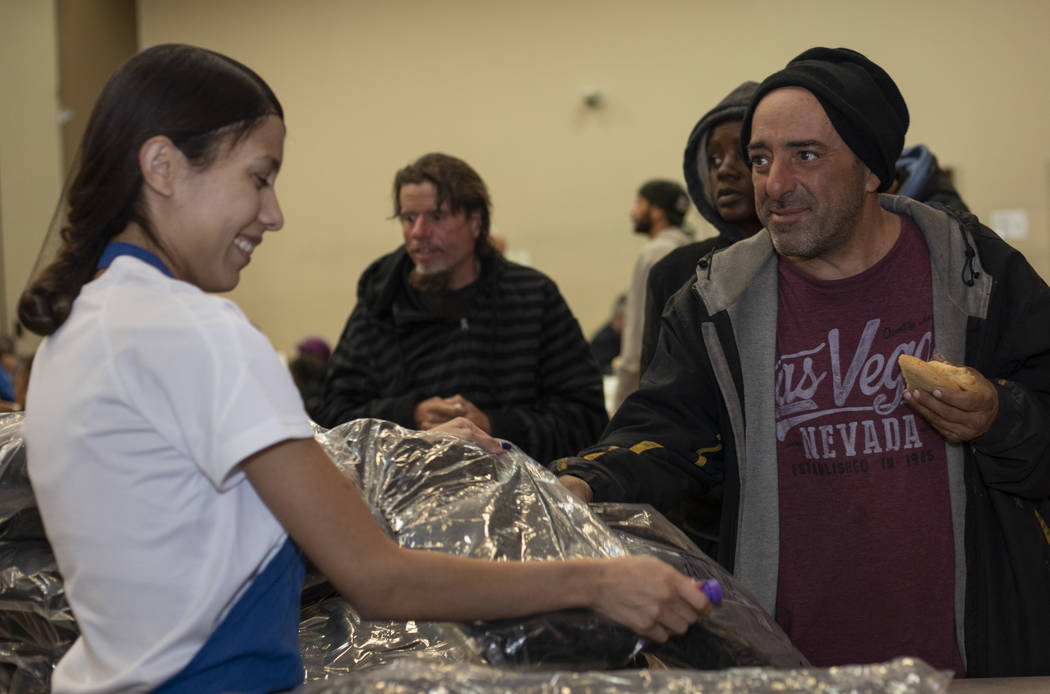 UNLV student Vicky Castellanos hands a CITYPAK backpack to Victor de Mayo at the Las Vegas Resc ...