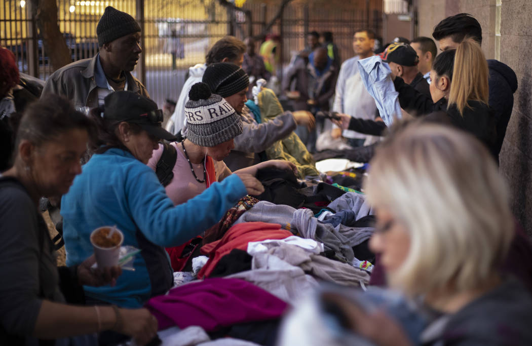 Homeless individuals sift through donated clothing after eating dinner at the Las Vegas Rescue ...