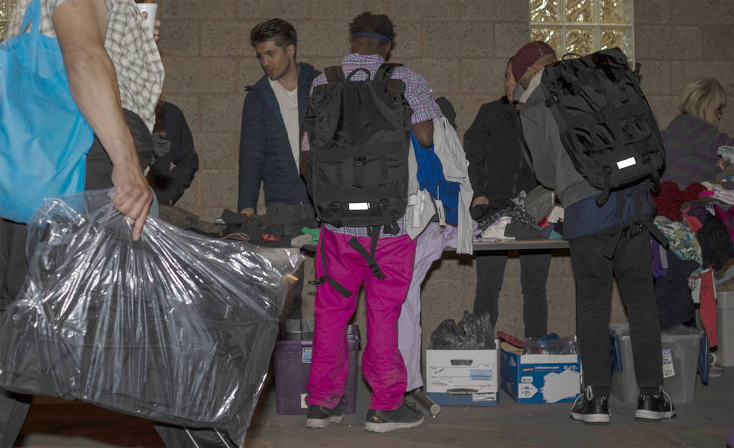 Two individuals wear CITYPAK backpacks as they look through donated clothing as a person walks ...