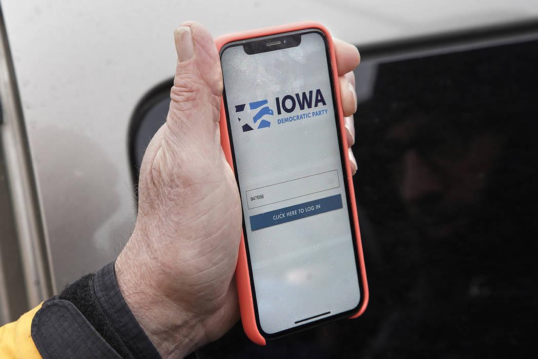 Precinct captain Carl Voss of Des Moines displays the Iowa Democratic Party caucus reporting ap ...
