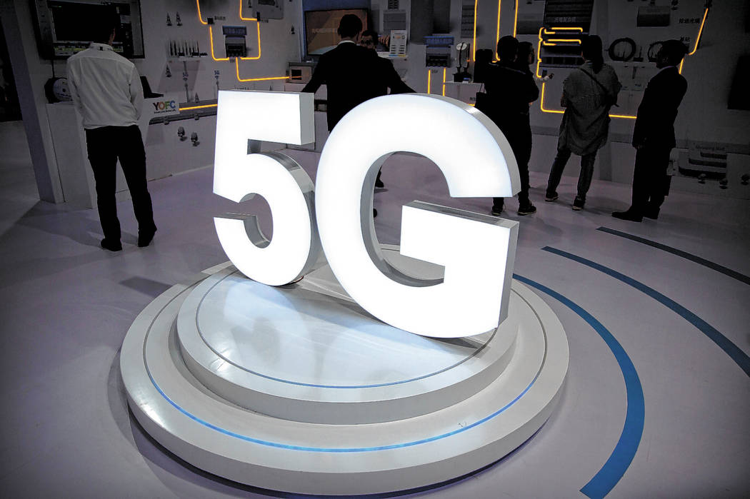 FILE- In this Sept. 26, 2018, file photo visitors stand near a 5G logo at a display the PT Expo ...