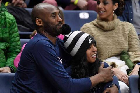Kobe Bryant and his daughter Gianna watch the first half of an NCAA college basketball game bet ...