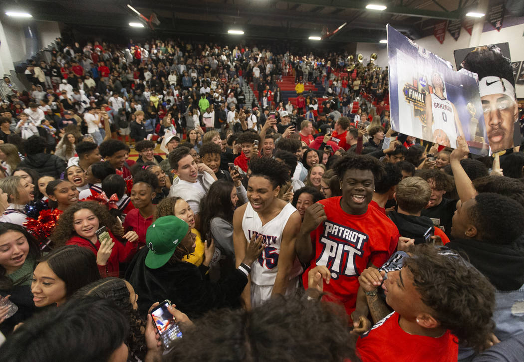 Liberty fans rush the court after the Patriots defeated Coronado on Friday, February 7, 2020, a ...