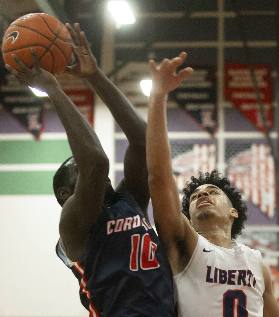 Liberty senior guard Julian Strawther (0) contests the shot of Coronado senior guard Tyrelle Hu ...