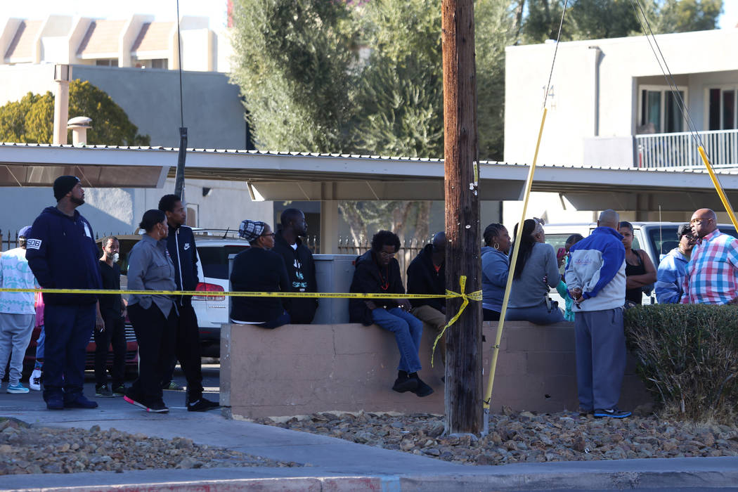 People watch as police investigate a homicide in a shopping center at the intersection of Swens ...